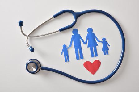 ostetoscope와 종이 가족 의학의 개념 가족과 심장 흰색 테이블에 잘라 내기. 평면도. 가로 조성입니다.