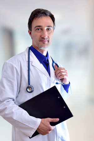 Caucasian general doctor with black clipboard. Front position half body. Vertical composition. Stock Photo