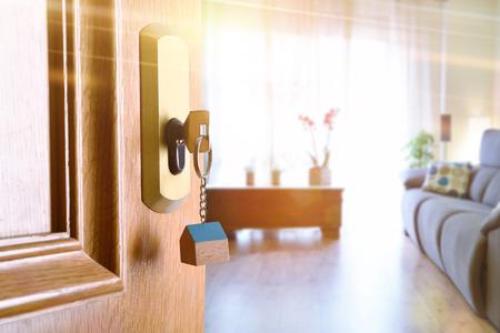Aprire la porta dell & # 39 ; ingresso dettaglio di una casa con chiavi in blocco e soggiorno illuminato in background con effetto luce oro Archivio Fotografico - 87487210