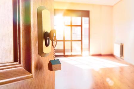 Détail de la porte d'entrée ouverte d'une maison avec les clés dans la serrure et la pièce vide à l'arrière-plan avec effet de lumière dorée Vue latérale Banque d'images - 87487213