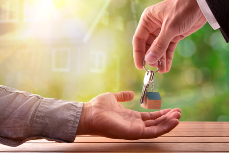 Agent giving the keys to the buyer of a house with house on nature background Stock Photo