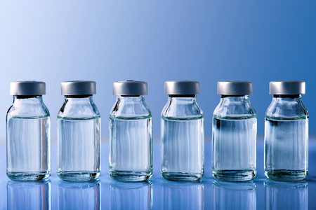 Row of vials with medication on blue methacrylate table. Horizontal composition. Front view.
