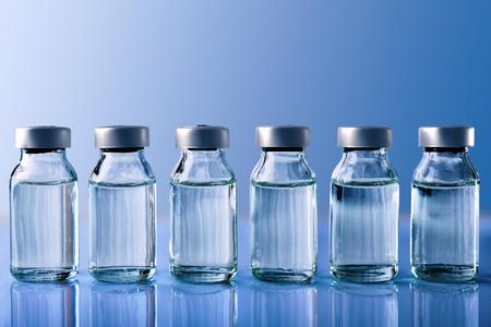 Rij van flesjes met medicijn op blauwe methacrylaatlijst. Horizontale samenstelling. Vooraanzicht. Stockfoto