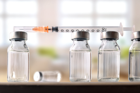 ampule: Row of vials with medication and syringe on white methacrylate table with window background. Horizontal composition. Front view.