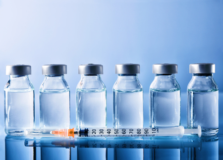 Row of vials with medication and syringe on blue methacrylate table. Horizontal composition. Front view.