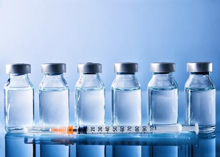 Fila de viales con medicación y jeringa en la mesa de metacrilato azul. Composición horizontal Vista frontal.