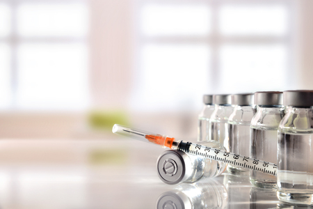 Los viales agrupan con la medicación y la jeringuilla en la tabla blanca del metacrilato con el fondo de la ventana. Composición horizontal Vista frontal.
