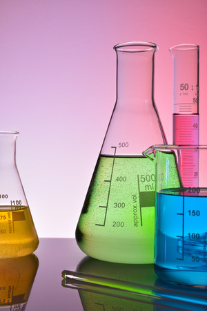 Laboratory glass chemical containers on glass table isolated colorful. Vertical composition. Front view Stock Photo