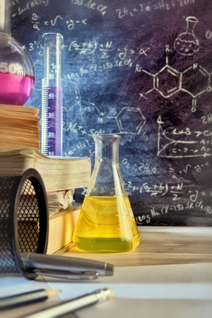 Classroom desk and drawn blackboard of chemistry teaching with books and instruments. Chemical sciences education concept. Vertical composition. Front view