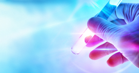 Science and research concept with hand of a scientist with test tube on blue background