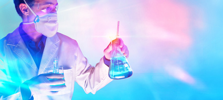 Worker equipped with protective elements and laboratory chemical material with blue red lights background. Horizontal composition. Stock Photo