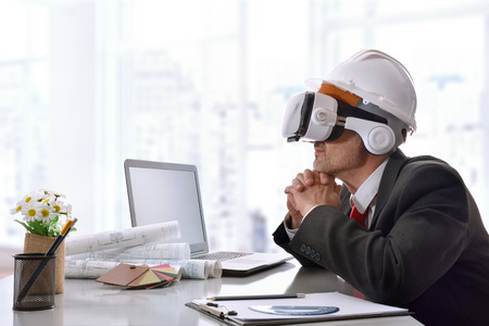 Architect watching 3d content in virtual reality glasses in the office. Horizontal composition. Stock Photo