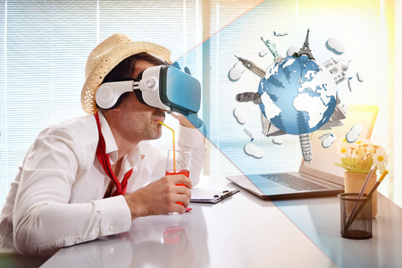 Man at work imagining his vacation virtually with virtual reality glasses with representation of monuments around the world. Horizontal composition Stock Photo