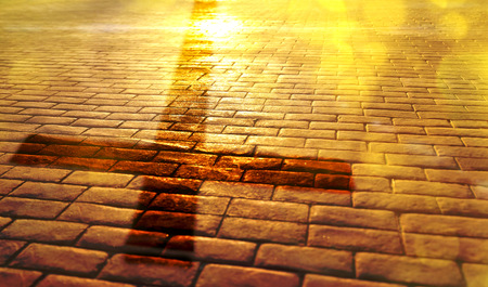 Representation of the way of salvation in the Christian religion with shadow of the cross on stone slabs and golden reflection of the sun Foto de archivo