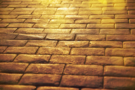 Road background of stone slabs with sun reflection and golden glitters close up. Religious and meditation concept.