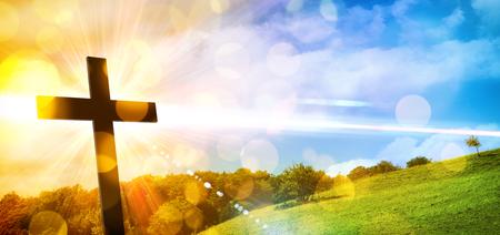 Religijna ilustracja z podświetlanym krzyżem ze złotym brokatem i bokeh i tłem krajobrazu przyrody. Kompozycja pozioma