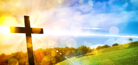 Religious illustration with backlit cross with golden glitter and bokeh and nature landscape background. Horizontal composition Imagens