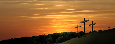 Religious illustration with three backlit crosses with golden glitter and bokeh and nature landscape background. Horizontal composition