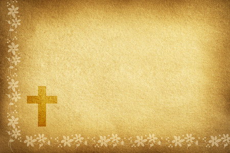 Religious card with brown textured fabric background decorated with flowers and cross.