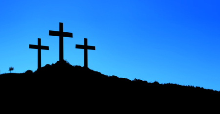 Religious illustration with three backlit crosses on a hill and blue sky. Horizontal composition