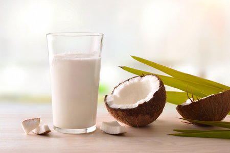 Coconut milk in glass with fruit on wooden table on a white kitchen background. Alternative milk concept. Front view. Horizontal composition.