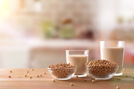 Reptientes with soy milk and grains on a wooden table and rustic kitchen background. Alternative milk concept. Front view. Horizontal composition