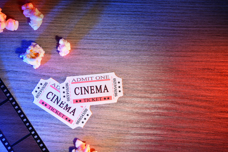 Equipment and elements of cinema on wooden table with colored lights. Concept of watching movies. Horizontal composition. Top view. Foto de archivo