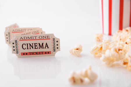 Cinema moments concept with popcorn and movie tickets on white background close up. Horizontal composition. Front view.