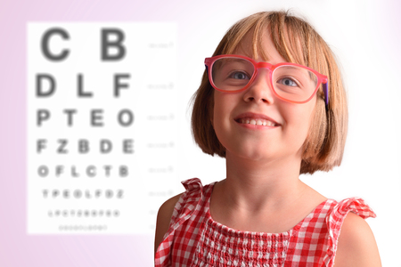 Child eye check with girl with glasses and letter board in the background. Concept of eye revision. Horizontal composition Archivio Fotografico