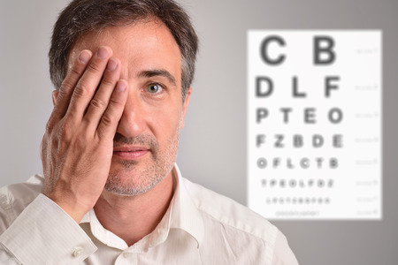Middle-aged man covering an eye for optical revision with letter chart in the background. Horizontal composition Reklamní fotografie