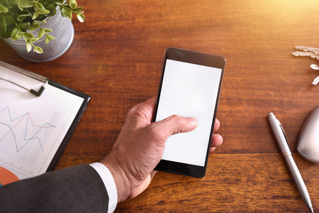 Businessman touching a smartphone on brown wood table in the office. Horizontal composition. Top view 免版税图像