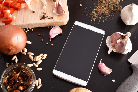 Preparation of vegetables on black wooden table with white mobile. Concept of recipes in digital book. Horizontal composition. Top elevated view
