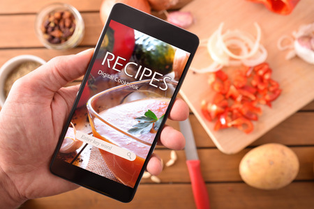 Smartphone with online recipes app and ingredients background. Use of the digital devices to cook. Horizontal composition. Top view 스톡 콘텐츠