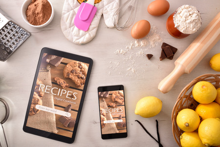 Dispositivi con app di ricette online e sfondo di ingredienti di pasticceria. Utilizzo dei dispositivi digitali per cucinare. Concetto di ricette nel libro digitale. Composizione orizzontale. Vista dall'alto