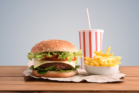 Beef burger,chips and soda on wooden table with golden backgorund. Front view. Horizontal composition. Imagens