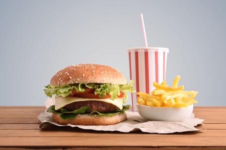 Hamburguesa de ternera, patatas fritas y refrescos en mesa de madera con fondo dorado. Vista frontal. Composición horizontal. Foto de archivo