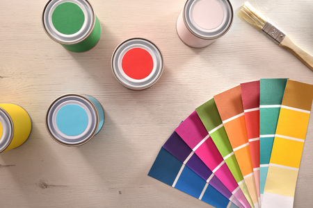 Colored paints and color palette on white table for renovation of materials. Top view. Horizontal composition.