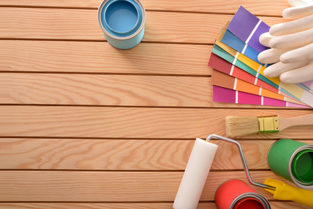 Colorful paint pots open and tools on wood table for renovation of materials and do home work. Home diy concept. Top view. Horizontal composition.