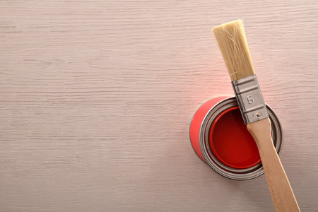 Can of red paint opened with brush over on a wooden table. Top view. Horizontal composition. Standard-Bild - 117378479