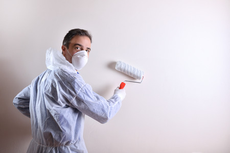 Background with professional painter with working overalls and roller on the back of a white wall looking down his back. Concept of painter and paint supplies. Horizontal composition.