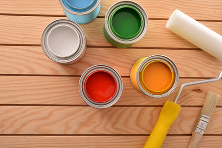 Colorful paint pots open on wood table for renovation of materials and do home work. Home diy concept. Top view. Horizontal composition. Standard-Bild - 117378485