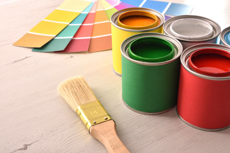 Colorful paint pots open and color palette on white table for renovation of materials. Elevated view. Horizontal composition. Standard-Bild - 117378486