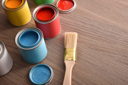 Assortment open paint cans and their covers and brush on wooden table. Top elevated view. Horizontal composition. Standard-Bild - 117378521