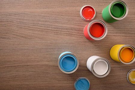 Five open paint cans and their covers on wooden table. Top view. Horizontal composition. Standard-Bild - 117378522
