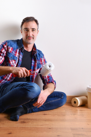 Man sitting on a parquet floor prepared with paint material to repaint his house. Front view. Vertical composition. Banque d'images - 117378525
