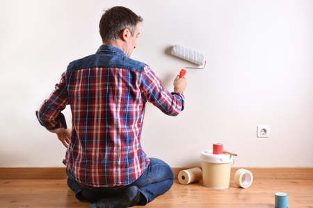 Man kneeling on a parquet floor with paint material painting his house. Front view. Horizontal composition. Standard-Bild - 117378527