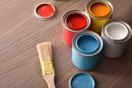 Assortment open paint cans and their covers and brush on wooden table. Top view. Horizontal composition. Standard-Bild - 117378531