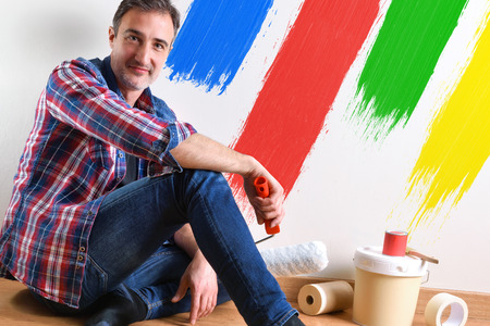 Man sitting on a parquet floor prepared with paint material to repaint his house and wall painted with colors close up. Front view. Horizontal composition.