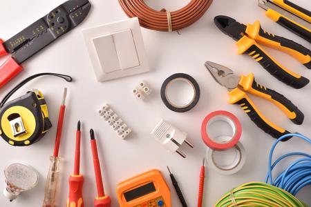 Herramientas y material eléctrico en una vista general de mesa blanca Composición horizontal. Vista superior. Foto de archivo