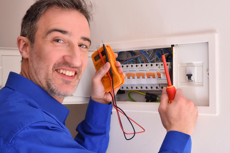 Smiling electrician with tester and screwdriver making repairs in electrical housing box